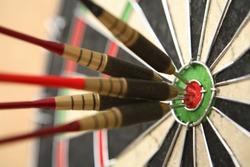 Five darts hitting bullseye on dartboard