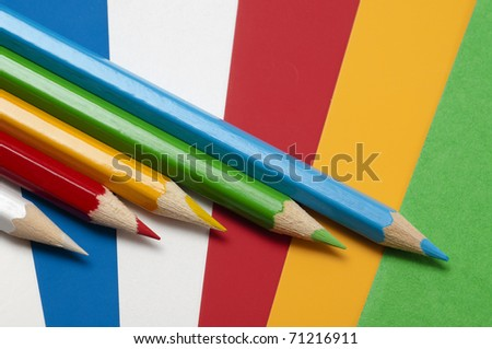 Five different colored pencils on different colored pieces of paper