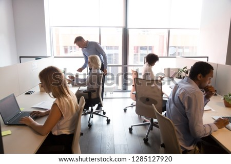 Five different multi-ethnic employees sitting at shared desk in modern light cozy coworking space working using computers having busy workday. Corporate teamwork common aim every day routine concept