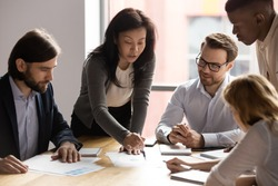 Five diverse business workgroup designers team with asian woman leader discuss paperwork financial report statistical data, forecasting working on common project. Brainstorm, briefing activity concept