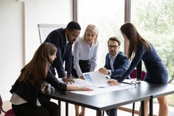 Five diverse focused employees make project research at group meeting. Expressing professional opinion, offering solution, working on analysis, reviewing statistics financial data do paperwork concept