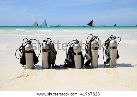 five diving tanks on the white beach with the sailboats in the background