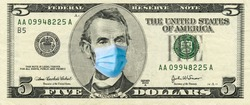 Five dollar bill with medical face mask on Abraham Lincoln