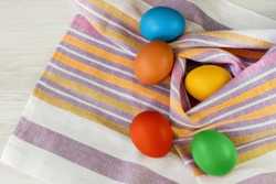 Five Easter eggs painted with multi-colored paints lie randomly in a striped towel on a wooden background close-up. Decoration for the holiday of Easter.