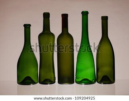 Five empty wine bottles  on  brown   background.