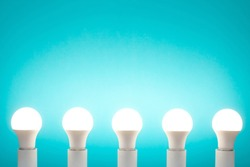 Five energy-saving white LED bulbs in a row on a blue background. All lamps are on.
