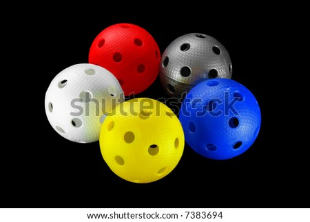 Five floorball balls isolated on a black background (white, blue, yellow, red and silver)