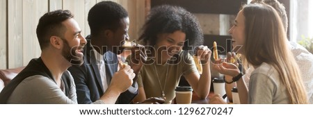 Photo of Five friends drinking coffee eating pizza at cafe, diverse people laughing tell jokes having fun in public place, multiracial friendship free time concept, horizontal banner for website header design