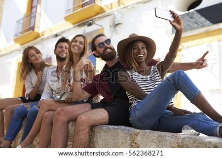 Five friends sitting on a wall in Ibiza taking a selfie #562368271