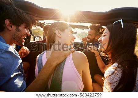 Five friends travelling together on a road trip in a car