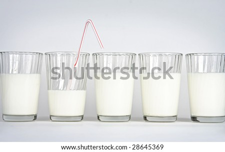 Five glasses on a white background with milk