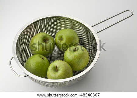 Five Granny Smith Apples in a Colander