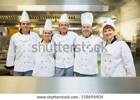Five happy chefs smiling at the camera in a kitchen wearing uniforms