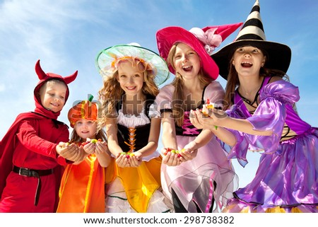 Five Happy Children Holding Candies in Halloween Costumes of Witches, Pumpkin and Devil at the Blue Sky