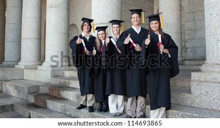 Five happy graduates posing the thumb-up in front of the university