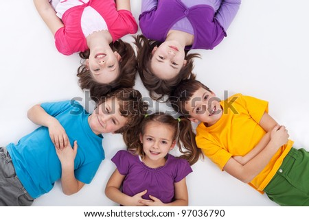 Five happy kids on the floor laying in circle
