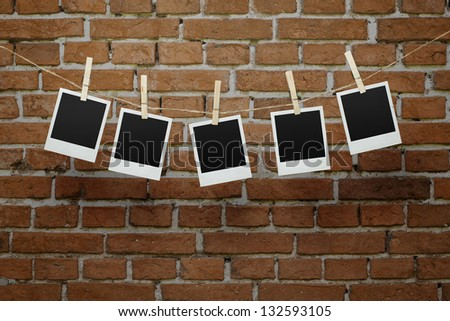 Five instant blank photographs hanging on a clothesline over brick wall with clipping path for the inside of the frames