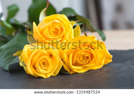 Five large buds of yellow roses. Bouquet of flowers. Sunny yellow garden roses on a black plate. Love theme. Celebration. Postcard