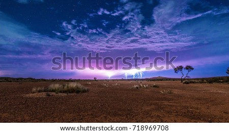 Five lightnings on a cloudy sky full of stars with the red dry soil of the outback desert under it. Thunderstorm lightning.