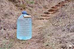 five-liter containers with clear clean drinking water on the side of the road, near the stairs. plastic bottle with water. Collected spring water