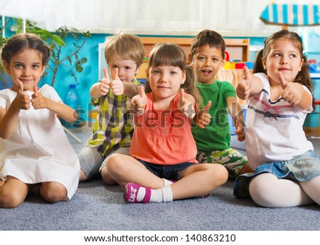 Five little children sitting on floor with thumbs up sign
