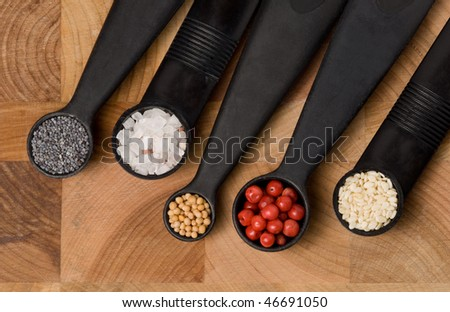 Five measuring spoons on a cutting board with various spices