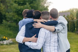 Five men is hugging and making a group photo. Outdoor, nature, party time.
