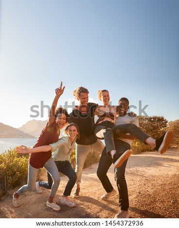Five millennial friends on a road trip have fun posing for photos on a coastal path, full length