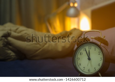 Five minutes before midnight 24.00 pm. Close-up of Retro alarm black clock vintage classic style on the bed room in home. light background from Bedside  lamp, time for sleep.
