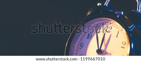 Five minutes to midnight. Changing the clocks, time adjustment, daylight savings or new year concept on retro analog clock, wide copy space background for internet banner #1199667010