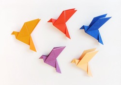 Five multi color Origami Birds are flying leading by an orange bird, isolated on white.