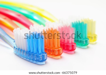 Five multicolored toothbrushes over white background