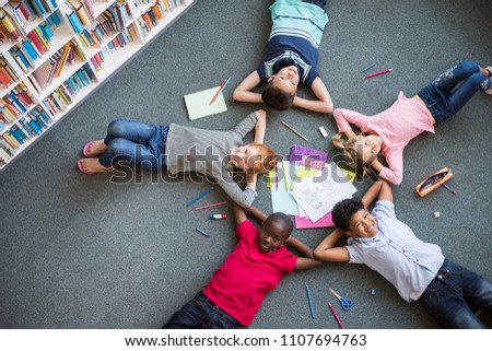 Five multiethnic children lying in circle on the floor and looking at camera. Top view of young boys and girls lying on back with drawing material. Portrait of happy smiling kids in library.