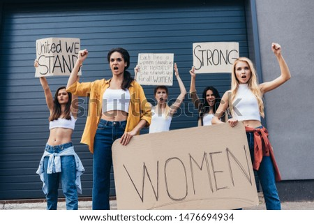 five multiethnic feminists holding placards with slogans and screaming on street
