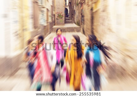 Five multiracial young girls on the streets of Palermo, Italy running in the historic city centre - radial zoom effect defocusing filter applied, with vintage instagram look