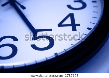 Five o clock - detail of wall office clock showing it's time to go home. Selective focus on number 5, blue tint