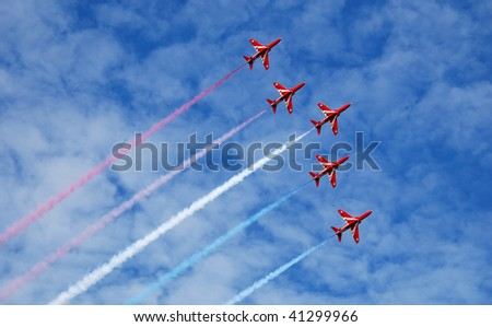 Five of the RAF display team The Red Arrows fly in formation across a summer sky.