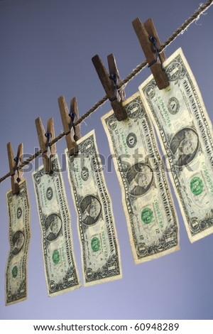 five one dollar bills hanging on a clothesline