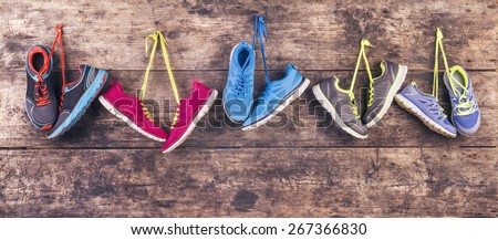 Five pairs of various running shoes hang on a nail on a wooden fence background