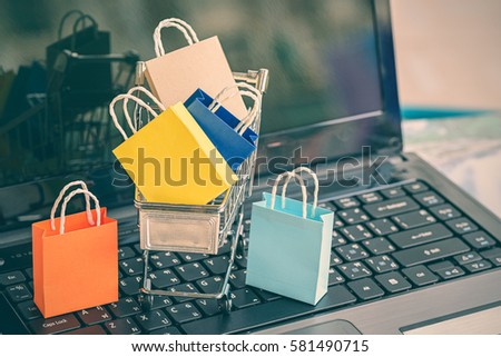 Shutterstock Five paper shopping bags in and out side a shopping cart on a laptop keyboard. Ideas about fraud when buying goods online from internet, hackers can hack or steal personal information easily nowadays.