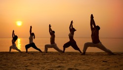 Five people practising yoga at the beach - warrior I pose.