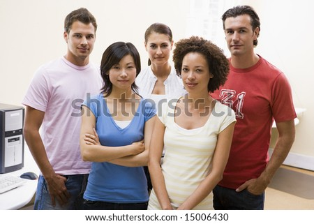 Five people standing in computer room - stock photo