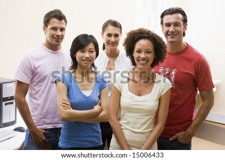 Five people standing in computer room smiling