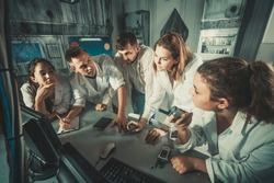 Five positive italian adults solving conundrums together in quest room in view as abandoned lab