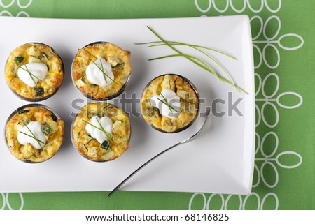 Five quiche appetizers with sour cream and chives.