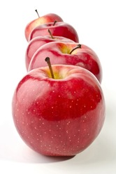 Five red apples lined up in a straight line isolated on a white background