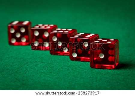 five red casino dices on a green table