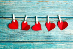 Five red hearts on wooden pegs on a rope on a blue wooden background, Valentines Day theme. Free space for text