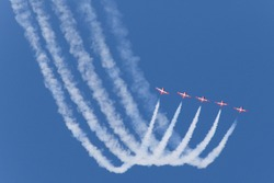 Five red jets leave white smoke trails while performing at a major North American airshow.