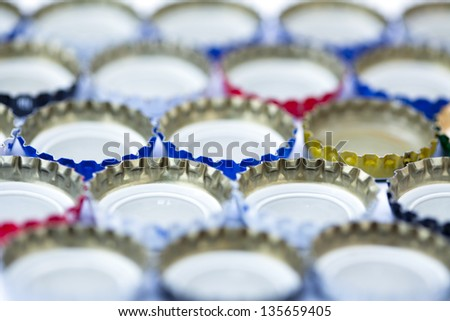 Five rows of metal bottle caps aligned upside down. Shallow depth of field.